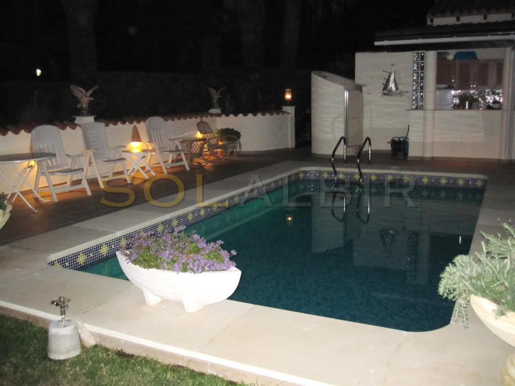 The lovely pool area with the outdoor kitchen