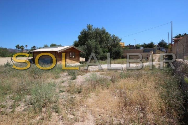 large plot with wooden house