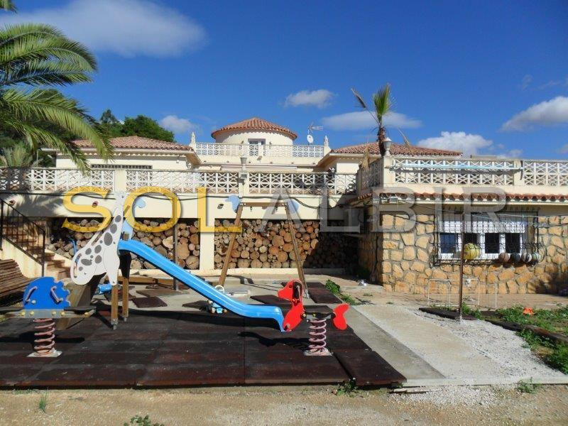 Back facade of the house with playground area