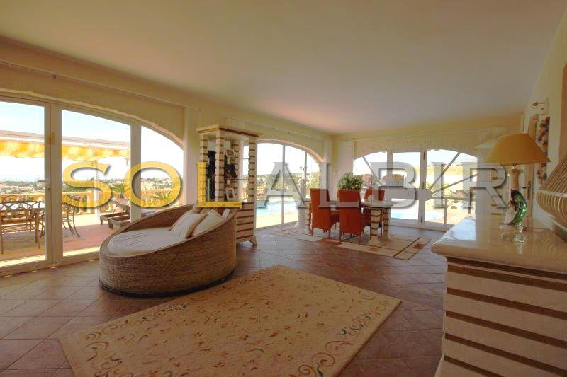 The in glassed living room with direct access to the pool area